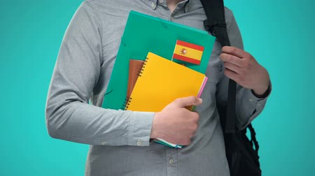 agglegény : Student holding notebooks with Spanish flag, international education program