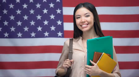 písanka : Cheerful Asian girl smiling with books against USA flag background, education