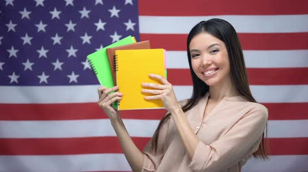 özel öğretmen : Asian girl smiling against USA flag background, student holding copybooks Stok Video