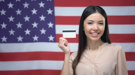bandeira americana : Lady holding credit card against USA flag background, international banking