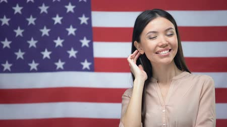 migrants : Positive Asian woman standing against USA flag background, independence day