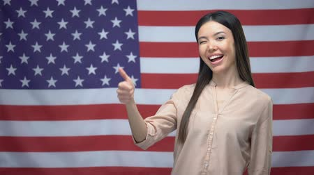 polegar : Happy Asian woman showing thumbs-up and winking against USA flag background