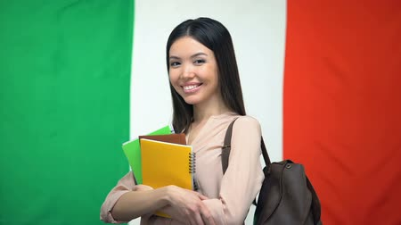 uitspraak : Female student standing with copybooks against Italian flag on background