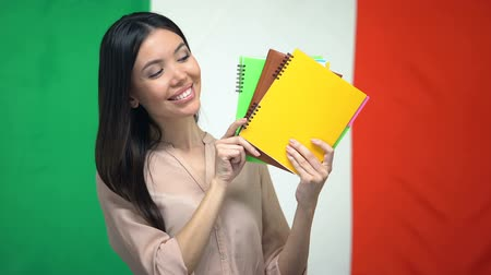 písanka : Smiling female showing copybooks against Italian flag, foreign language courses