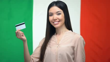 job transfer : Positive woman holding credit card against Italian flag, money transfer service