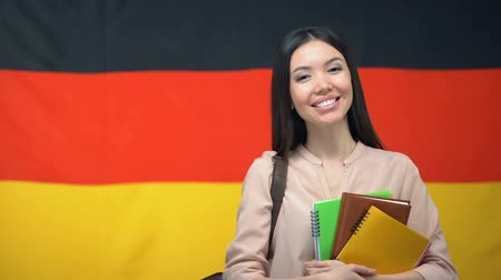 písanka : Happy female student holding copybooks against German flag background, education Dostupné videozáznamy