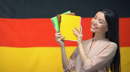 písanka : Cheerful female showing copybooks against German flag, foreign language courses