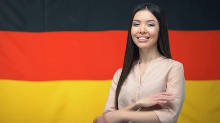 migrants : Asian woman standing with hands crossed against German flag on background