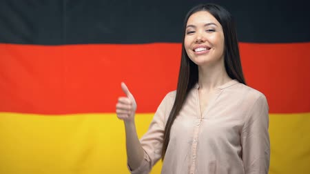 migrants : Beautiful Asian female showing thumbs-up sign against German flag background Stock Footage