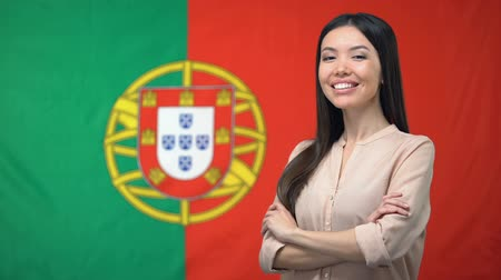 migrants : Smiling woman standing with hands crossed against Portuguese flag background Stock Footage