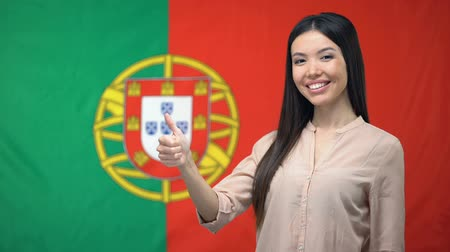 ilan : Pretty woman showing thumbs-up against Portuguese flag background, migration