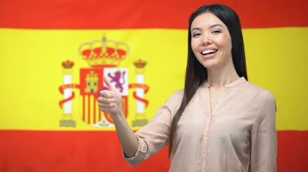polegar : Smiling Asian woman showing thumbs-up gesture against Spanish flag background