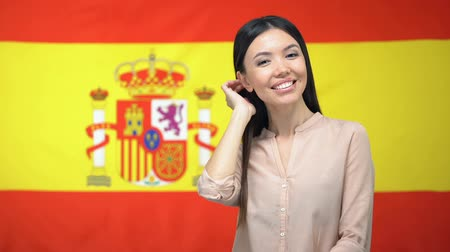 migrants : Beautiful woman looking at camera against Spanish flag background, tourism