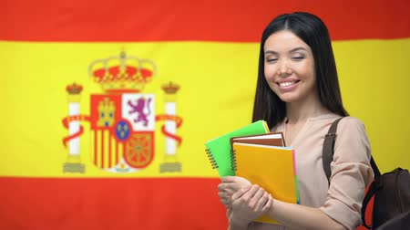 pronunciation : Cheerful Asian female student standing against Spanish flag, language studying Stock Footage