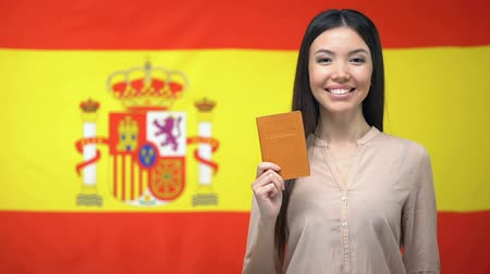 ulus : Smiling Asian girl holding passport against Spanish flag background, citizenship Stok Video