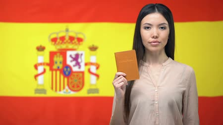 migrants : Serious Asian woman showing passport against Spanish flag background, migration