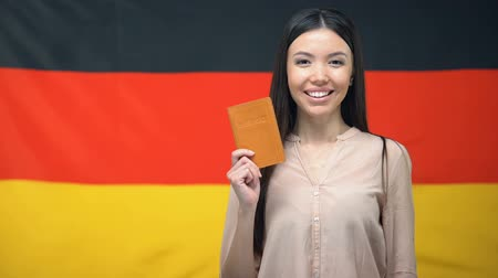 pasaport : Smiling woman holding passport against German flag background, migration