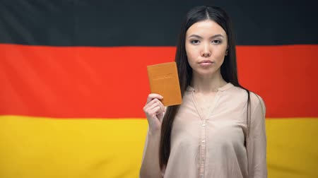 migrants : Serious Asian female showing passport against German flag background, close-up