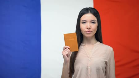 pasaport : Serious Asian female showing passport against French flag background, embassy
