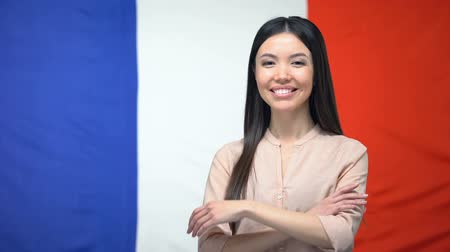 migrants : Cheerful Asian girl standing with hands crossed against French flag background Stock Footage