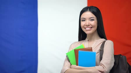 písanka : Female student holding copybooks against French flag, international education
