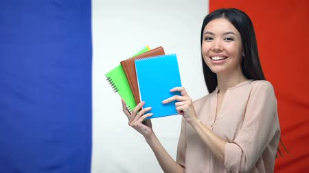 übersetzen : Smiling Asian lady showing copybooks against French flag background, lessons