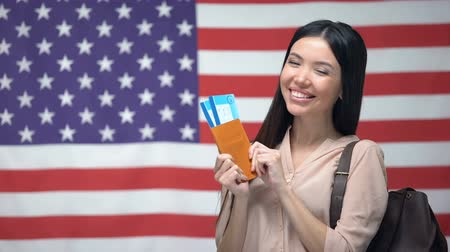 migrants : Excited woman holding passport and flight tickets against USA flag background
