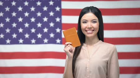 migrants : Adorable female showing passport against USA flag background, citizenship Stock Footage
