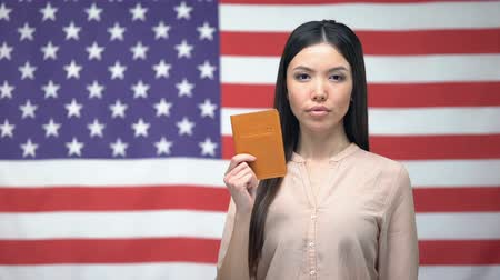 pasaport : Confident Asian woman showing passport against USA flag background, migration