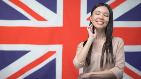 migrants : Smiling Asian woman standing against British flag, international friendship