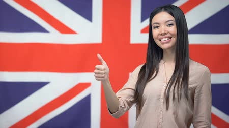polegar : Beautiful woman showing thumbs-up against British flag background, template