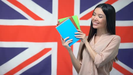 bretanha : Pretty female student showing copybooks against British flag, learning language Vídeos