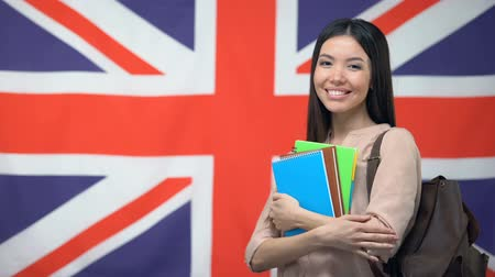 migrants : Cheerful Asian woman standing against British flag background, study abroad