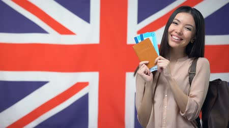 migrants : Happy female traveler holding passport with flight tickets against British flag