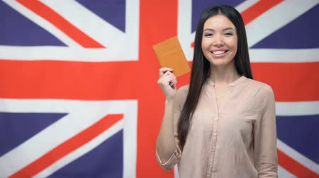 migrants : Smiling Asian girl holding passport against British flag background, citizenship Stock Footage