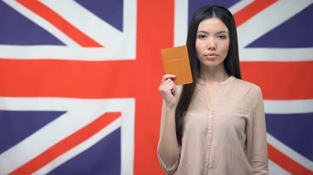 migrants : Confident Asian woman showing passport against British flag background, emigrant