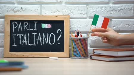 speaker : Do you speak Italian written on board, hand putting Italy flag in box, language