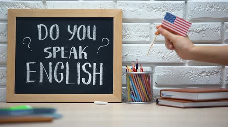 alto falante : Do you speak English written on board, hand putting USA flag in box, language Stock Footage