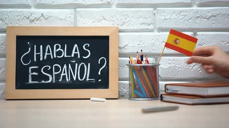 speaker : Do you speak Spanish written on board, hand putting Spain flag in box, language