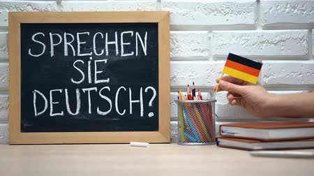 speaker : Do you speak German written on board, hand putting Germany flag in box, language