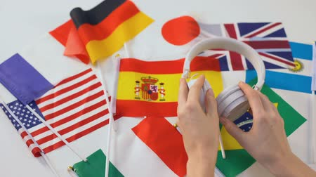özel öğretmen : Hands taking headset, different countries flags on table, language audio lessons
