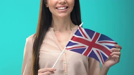 виза : Smiling woman holding Great Britain flag on blue background, education abroad
