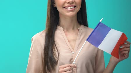 traduzione : Smiling woman holding French flag on blue background, student exchange program