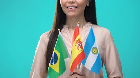 bandiera brasiliana : Young woman holding national flags of Brazil Spain Argentina, language school