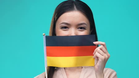 виза : Woman covering mouth by German flag, foreign university education, migration Стоковые видеозаписи
