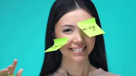 productiviteit : Happy female with sticky notes, learning body parts in Spanish, education Stockvideo