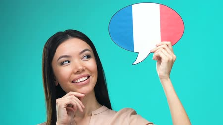 speaking : Dreaming pretty female holding French speech bubble, fluent foreign language