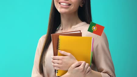 foreign national : Joyful young woman holding Portuguese flag notebooks, learning foreign language