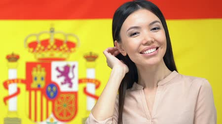 migração : Beautiful young woman smiling camera on Spanish flag background, patriotism