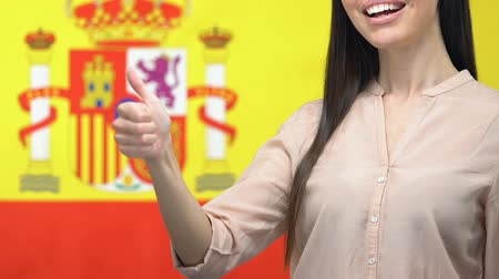 migração : Joyful female showing thumbs up closeup on Spanish flag background, work permit